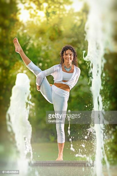 Yoga concept woman pose with water fountain