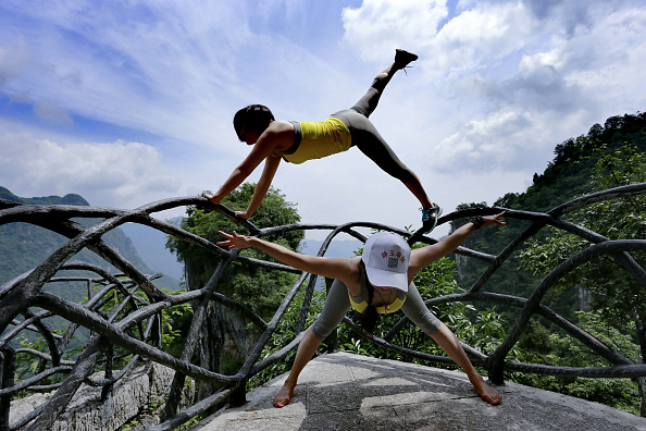Yoga enthusiasts perform yoga on a cliff plank road on May 24 2016 in Yichang Hubei Province of China The glass plank road along a 7500meterlong...