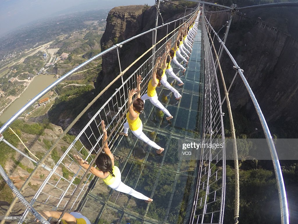 Yoga enthusiasts practice on a glass suspension bridge at the Shiniuzhai National Geological Park on November 5 2015 in Pingjiang County Yueyang City...