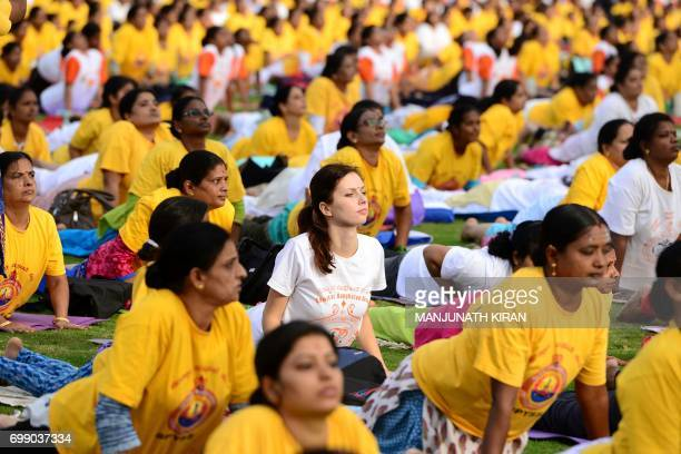 Yoga enthusiasts take part in a mass yoga session on International Yoga Day at the Shree Kanteerava Stadium in Bangalore on June 21 2017 Yoga has...