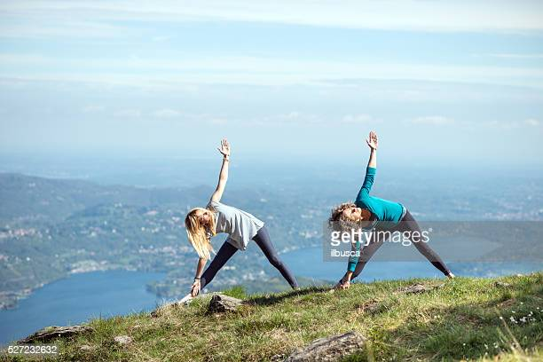 Yoga exercises in nature on mountains: triangle pose