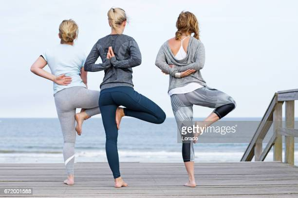 3 yoga female friends working out on daytime beach