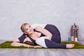 Yoga woman practicing yoga. Beautiful blonde woman in  sports jumpsuit doing yoga asana on the carpet in the studio.
