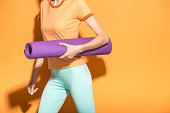 Yoga girl with yoga mat hurring to yoga class isolated over orange background