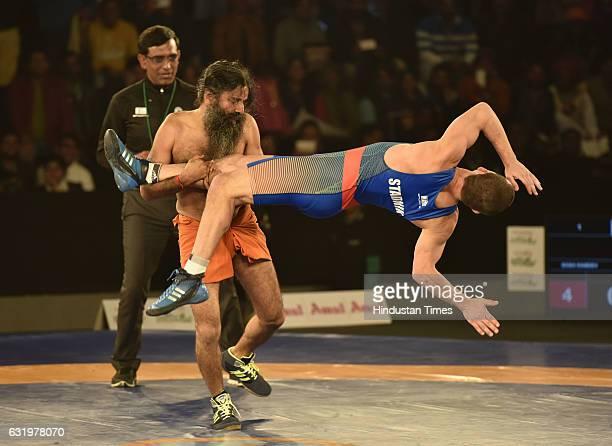 Yoga Guru Baba Ramdev and 2008 Olympic silver medallist Andrey Stadnik in action during the Pro Wrestling League2 at K D Jadhav Stadium IG Stadium on...