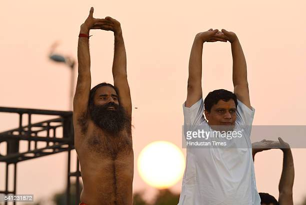 Yoga Guru Baba Ramdev and Acharya Balkrishna perform yoga during the rehearsals for the upcoming International Yoga Day at Rajpath on June 19 2016 in...