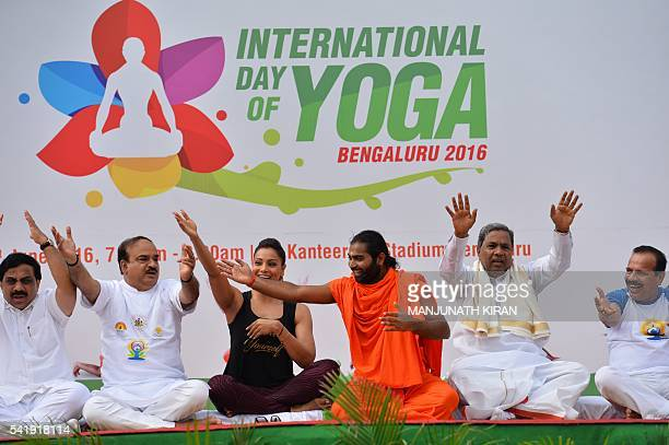 Yoga guru Vachanaananda conducts a laughter session with Chief Minister of Karnataka Siddaramaiah Union Minister for Fertilizer Ananth Kumar and...
