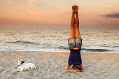 Young woman doing inverted posture - Sirsasana