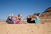 Two women doing yoga in the desert.