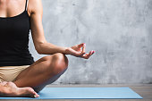 Yoga indoors. Woman in lotus position in sport loft, close up.