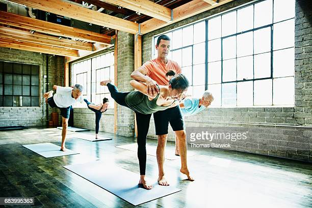 Yoga instructor adjusting student during class