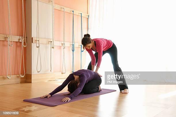 Yoga instructor adjusting student