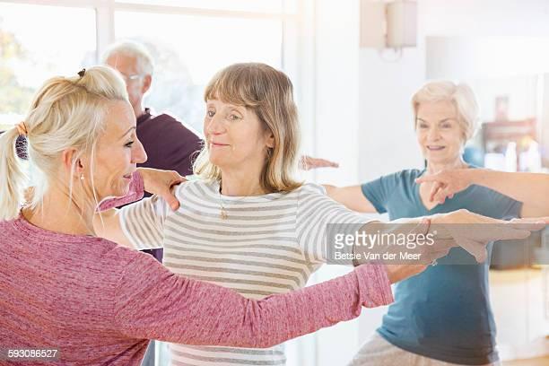 Yoga Instructor corrects senior woman's arm