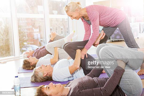Yoga instructor helps senior woman in class.