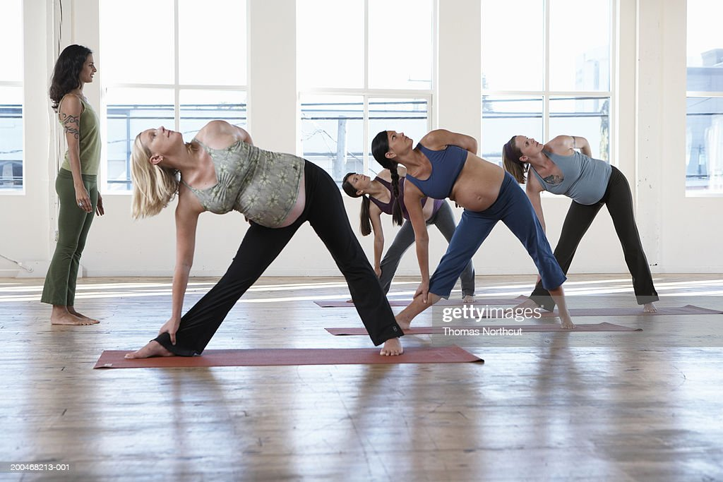 Yoga instructor teaching four pregnant women in yoga class