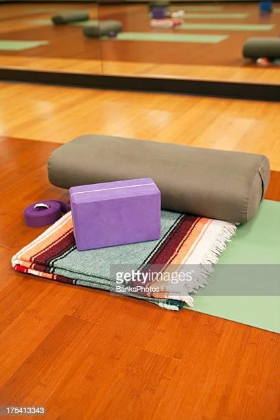 Yoga-Matte, einer Decke, einer Nackenrolle, Block und Riemen auf Studio-Etage