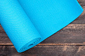 Yoga mat on a wooden background. Equipment for yoga. Concept healthy lifestyle. Copyspace. Selective focus