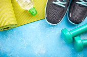 Yoga mat, sport shoes, dumbbells and bottle of water on blue background. Concept healthy lifestyle, sport and diet. Sport equipment. Copy space
