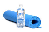 bottled water and blue yoga mat on white background