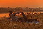 Man doing yoga on sunset with city view,Half Bow Pose/Ardha Dhanurasana. Toned image.