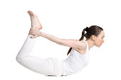 Sporty beautiful young woman in white sportswear doing backbend exercises, lying in dhanurasana, Bow Pose, studio full length side view, isolated