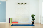 Yoga room with mat and white brick wall