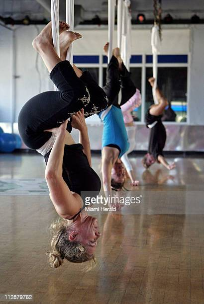 Yoga student Shari Portnoy foreground hangs up side down with the rest of the group during an Antigravity Yoga with Wings class at Crunch Fitness in...
