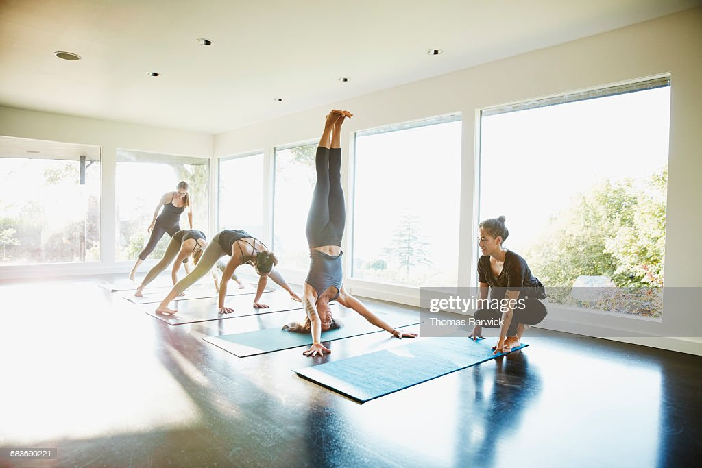 Yoga student warming up with headstand before class in studio