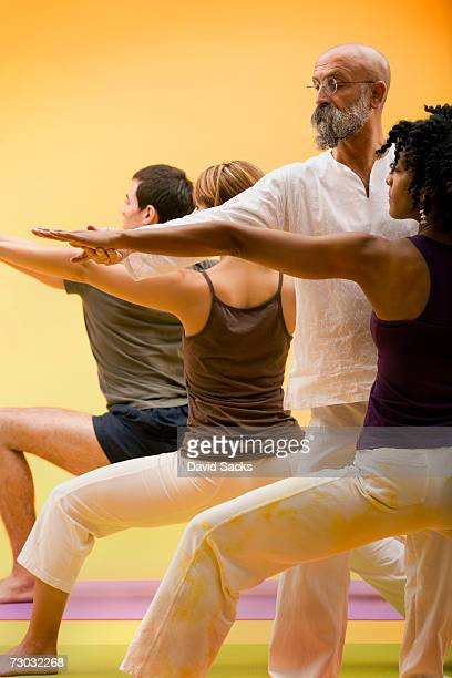 Yoga teacher helping student with pose in yoga class