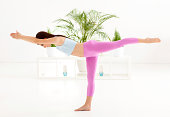 Woman practicing yoga at home - warrior pose.