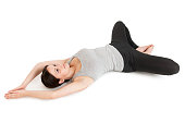 """Increased whole-body view of a lying on the back young woman in yoga position """"the Butterfly"""" (supta baddha konasana) on a white background."""
