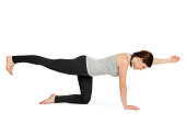 Side full body view of a young woman in front of white background the Yoga exercise showing diagonal cat (Majariasana).