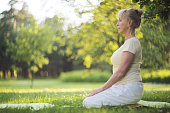 Beautiful mature woman practice yoga in summer park