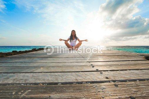 Yoga woman meditating near sea : Stock Photo