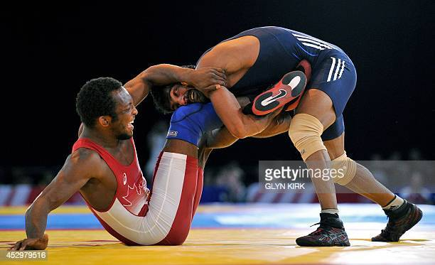 Yogeshwar Dutt of India grapples with Jevon Balfour of Canada in the Men's Freestyle 65kg Freestyle Wrestling Gold medal match at the SECC 2014...