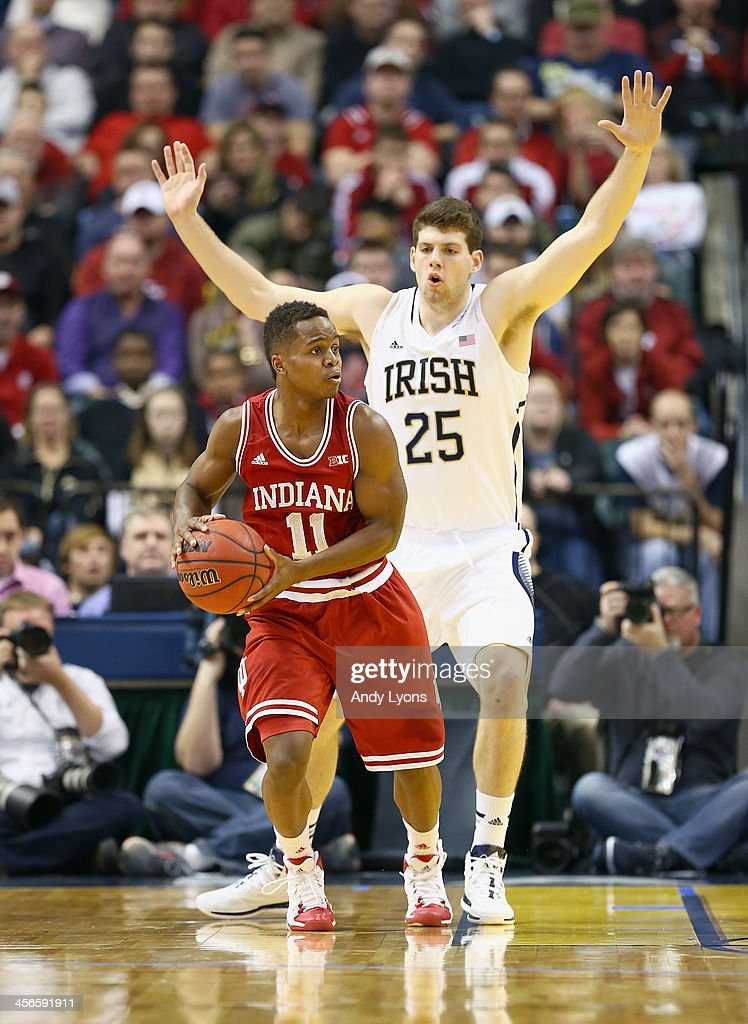 Yogi Ferrel #11 of the Indiana Hoosiers looks to pass the ball while defended byTom Knight #25 of the Notre Dame Fighting Irish during the 2013 Crossroads Classic at Bankers Life Fieldhouse on December 14, 2013 in Indianapolis, Indiana.