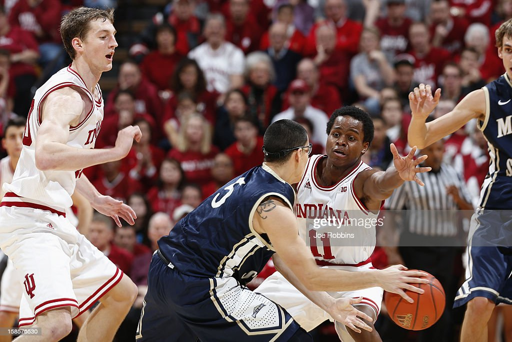 Yogi Ferrell #11 and <a gi-track='captionPersonalityLinkClicked' href=/galleries/search?phrase=Cody+Zeller&family=editorial&specificpeople=7621233 ng-click='$event.stopPropagation()'>Cody Zeller</a> #40 of the Indiana Hoosiers defend against Josh Castellanos #5 of the Mount St. Mary's Mountaineers during the game at Assembly Hall on December 19, 2012 in Bloomington, Indiana. The Hoosiers won 93-54.