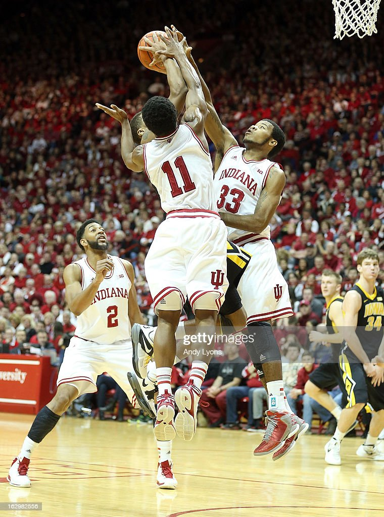 Yogi Ferrell #11 and Jeremy Hollowell #33 of the Indiana Hoosiers defend the shot of Roy Devyn Marble #4 of the Iowa Hawkeyes during the game at Assembly Hall on March 2, 2013 in Bloomington, Indiana.