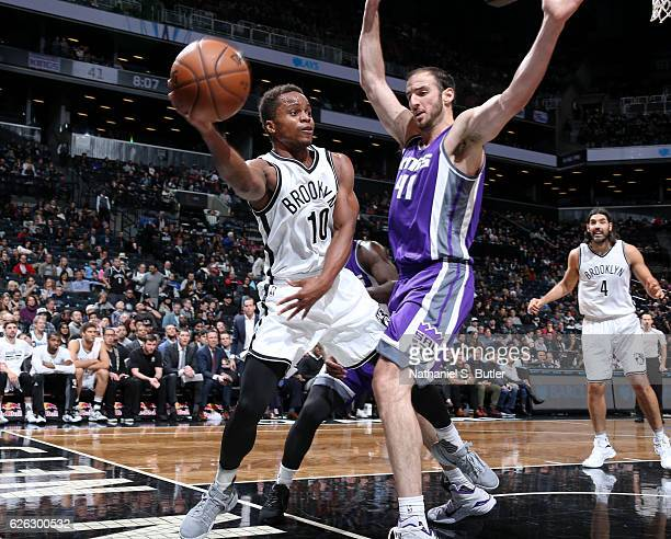 Yogi Ferrell of the Brooklyn Nets passes the ball while guarded by Kosta Koufos of the Sacramento Kings on November 27 2016 at Barclays Center in...