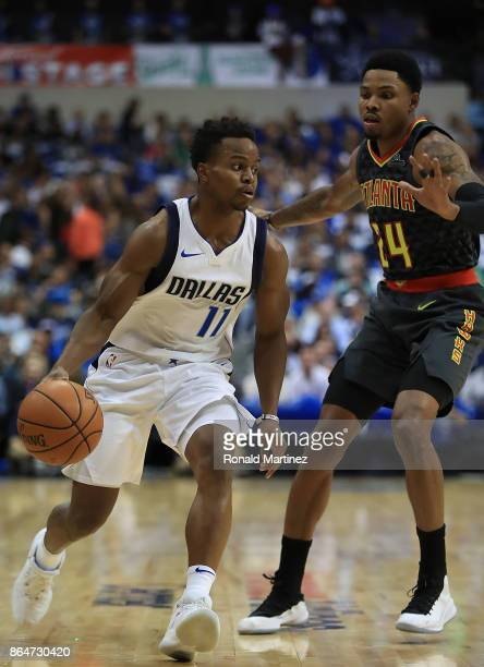 Yogi Ferrell of the Dallas Mavericks dribbles the ball against Kent Bazemore of the Atlanta Hawks at American Airlines Center on October 18 2017 in...