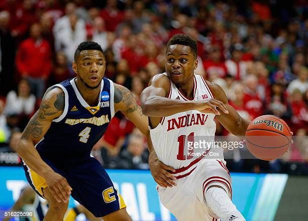 Yogi Ferrell of the Indiana Hoosiers drives against Johnathan BurroughsCook of the Chattanooga Mocs in the first half during the first round of the...