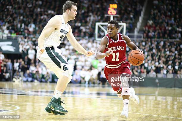Yogi Ferrell of the Indiana Hoosiers drives to the basket against Matt Costello of the Michigan State Spartans in the first half at the Breslin...