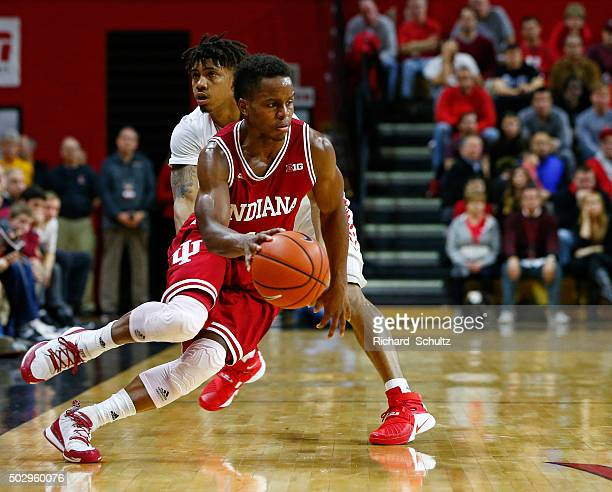 Yogi Ferrell of the Indiana Hoosiers is defended by Corey Sanders of the Rutgers Scarlet Knights during the second half of a college basketball game...
