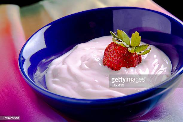 Yogurt and fresh ripe strawberry fruit in blue bowl