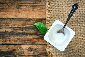Yogurt in a plastic white container, vintage spoon, green leaf, canvas napkin on a wooden table