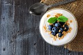 Yogurt with sweet blueberries and granola, above view on rustic dark wood