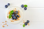 Greek yogurt with blueberries and granola, above view on white wood