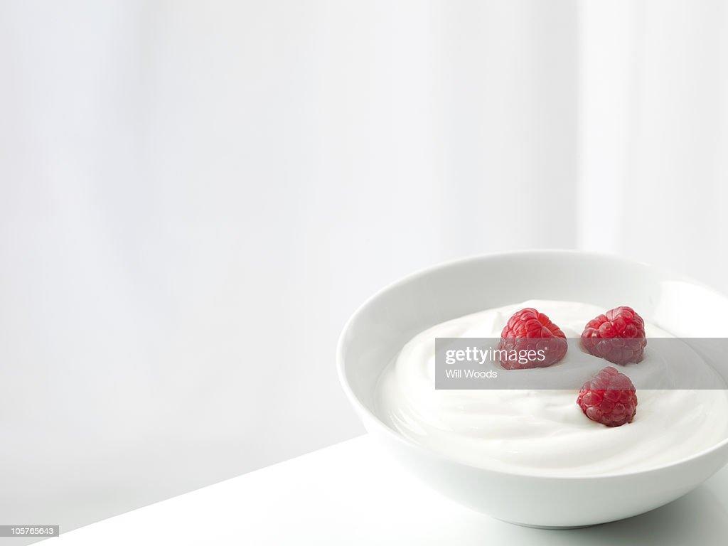 Yogurt with raspberries in a white bowl