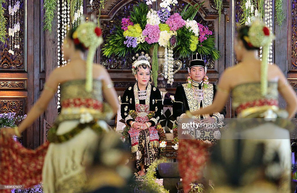 Yogyakarta Sultan Hamengkubuwono X's fourth daughter Princess Hayu (L), 29, and Prince Notonegoro, (R), 39, watch a Javanese traditional dance during the final day of the royal wedding ceremony at the sultan's palace in Yogyakarta, on Indonesia's island of Java on October 23, 2013. The three-day festive wedding ceremony follows the tradition of the Yogyakarta Sultanate since the ancient period. AFP PHOTO / LALA
