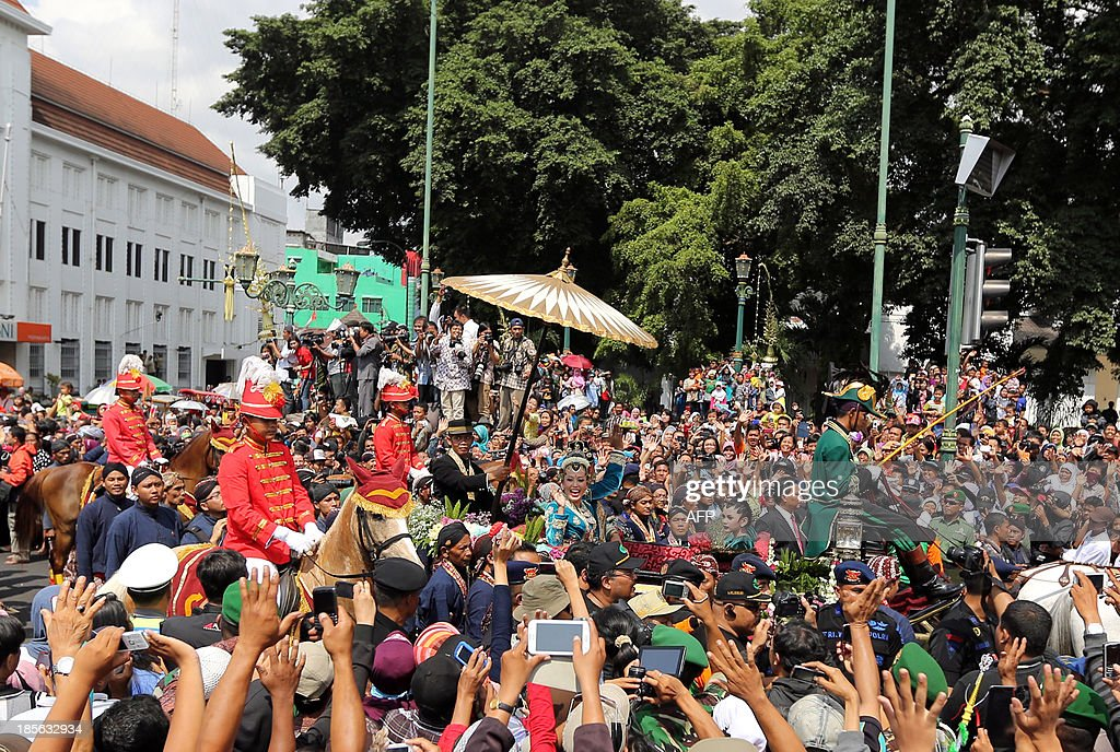 Yogyakarta Sultan Hamengkubuwono X's fourth daughter Princess Hayu, (C, under umbrella) with husband Prince Notonegoro ride a horse drawn carriage to greet thousands of well wishers during the final day of the royal wedding ceremony at the sultan's palace in Yogyakarta, on Indonesia's island of Java on October 23, 2013. The three-day festive wedding ceremony follows the tradition of the Yogyakarta Sultanate since the ancient period.